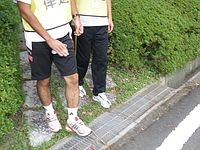アイマスク体験で不整地を案内、どぶ板(グラーチング)の上を介助する参加者の足もとの写真