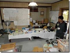8畳ほどのふつうの和室が本部、壁にはコース図が大きく張られて、前の実行委員長が移動先と連絡を取っています(パソコンや、携帯電話がたくさん置かれています)