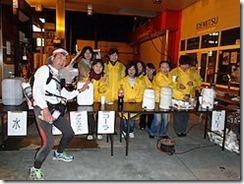 西寺交差点(44キロ)地点で、おなじみのボランティアさんと記念写真を写します(エイドの皆さんは黄色のスタッフジャンパーを着用して8人がいます。テーブルには「水」「アクエリアス」「コーヒー」などと書かれた紙が貼ってあります。筆者や画面の左端で左手を出してVサイン!、スタッフの皆さんの笑顔が素晴らしいです)