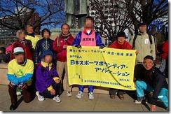 気清麻呂像まえでイベントの旗を持って記念写真を写す参加者とスタッフが十数名写っています。